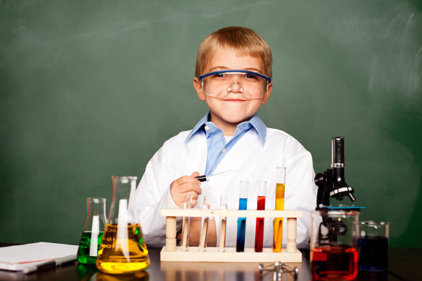 Young boy in lab coat with protective glasses on with test tubes in front, looking like a scientist