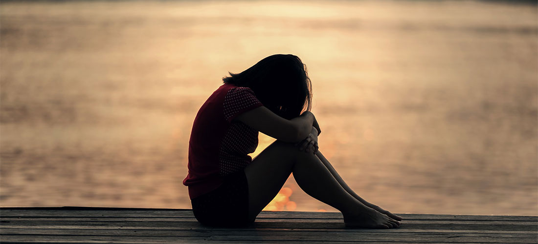 Teenage girl sitting on edge of a dock with head tilted down resting on her bent knees. Appears sad