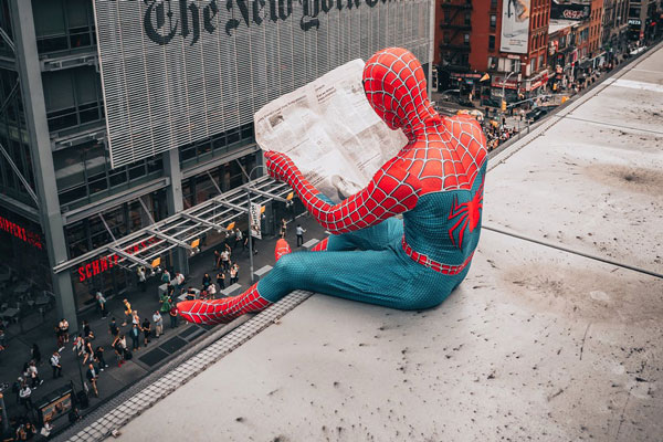Spiderman reading newspaper perched on building
