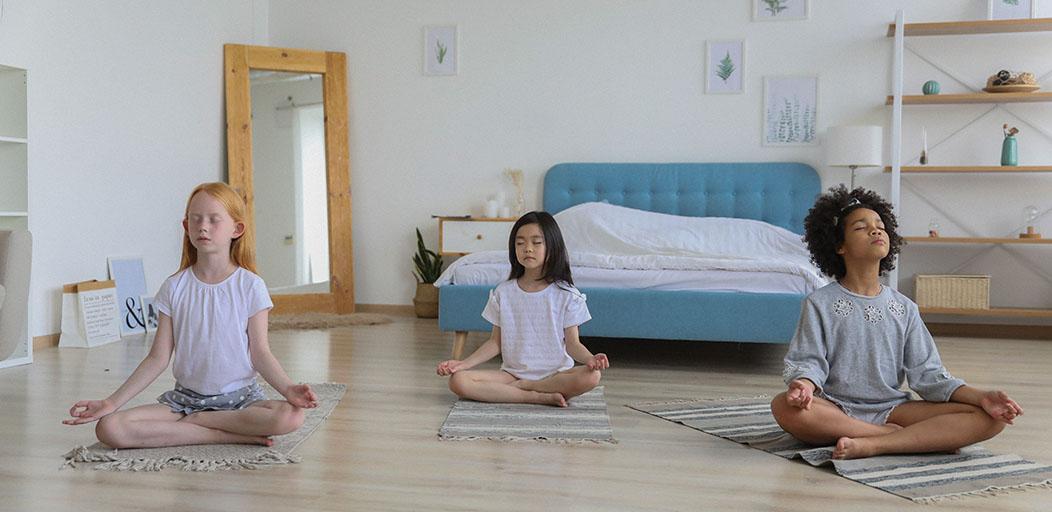 three girls of different ethnicities meditating