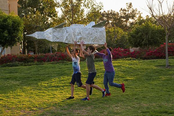 kids holding a homemade rocketship